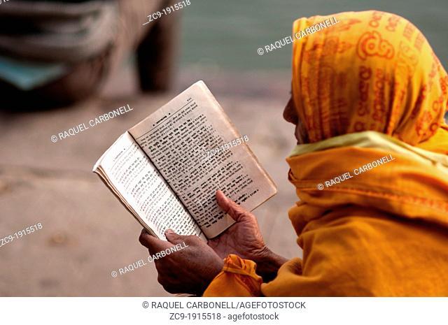 Woman reading on the ghats  Varanasi, Benares, Uttar Pradesh, India
