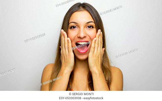 Excited and surprised happy woman shouts holds cheeks by hand. Beauty girl excited on white background. Expressive facial casual woman