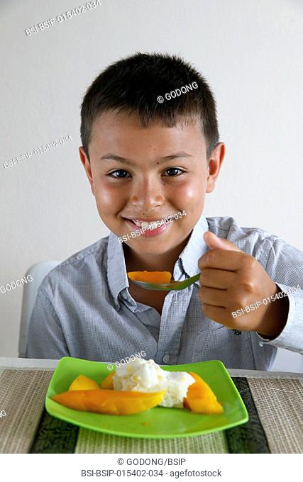 Boy eating sticky rice with mango. Thailand