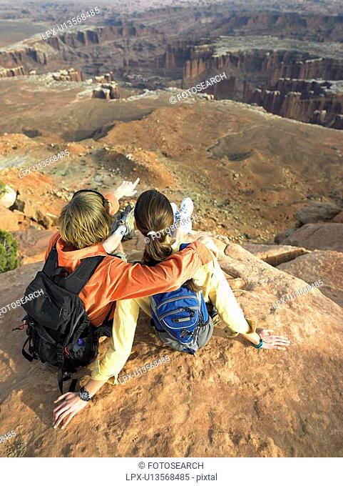 Young couple with backpacks looking at rock strata on cliff