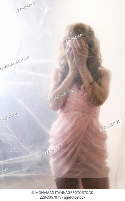 Scared woman wearing a pink dress hiding face with hands behind a plastic sheet