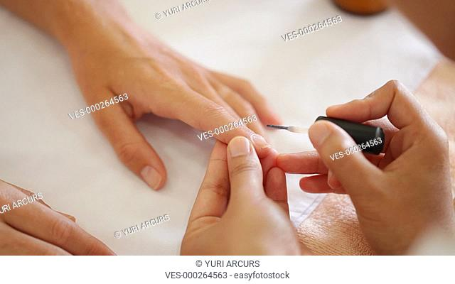 Closeup footage a beautician carefully appplying a clear nail treatment to the nails of a customer