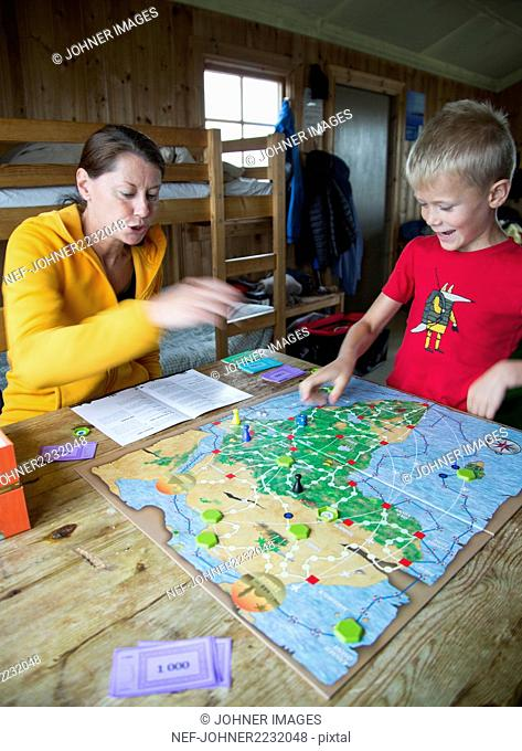 Mother with son playing board game