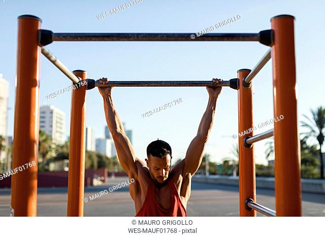 Fit man working out in climbing parcour, doing pull ups