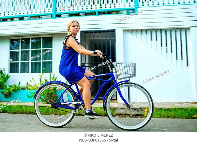 Panama, Bocas del Toro, Woman riding a bicycle, looking at camera