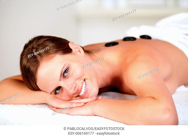 Close up portrait of a young female smiling and relaxing at spa, hot stone massage treatment