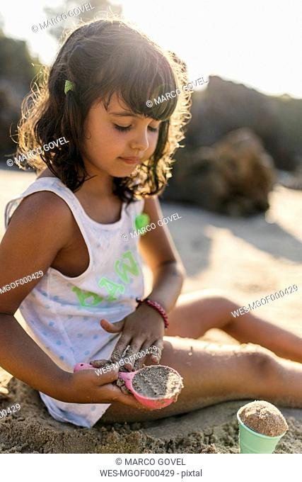 Spain, Llanes, little girl playing with sand on the beach