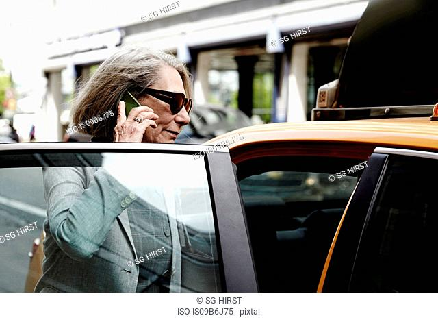 Senior businesswoman getting into taxi, using smartphone
