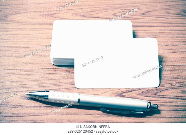 stack of business card with pen on wood background vintage style