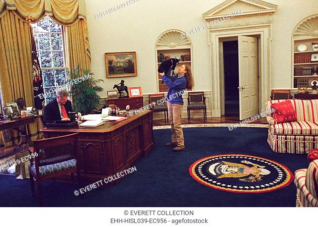 Chelsea Clinton Playing with Socks the Cat in the Oval Office. At left, President Bill Clinton Works at his desk. Dec. 24, 1994. (BSLOC-2015-2-201)