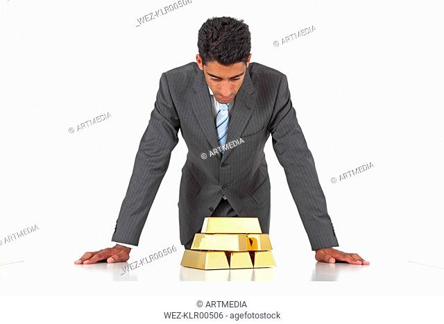 Man looking at gold bars