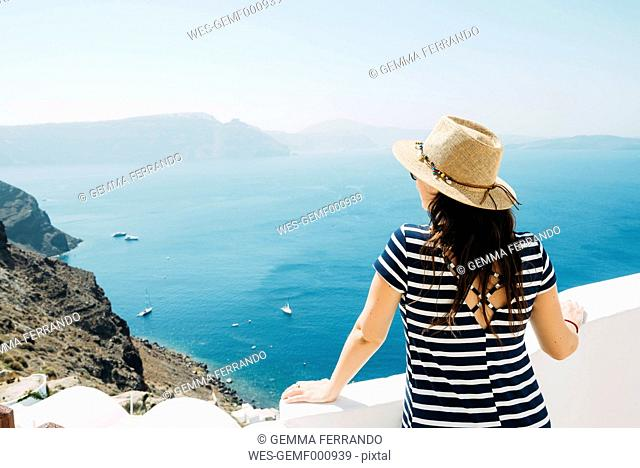 Greece, Santorini, Oia, back view of woman with straw hat looking to the sea