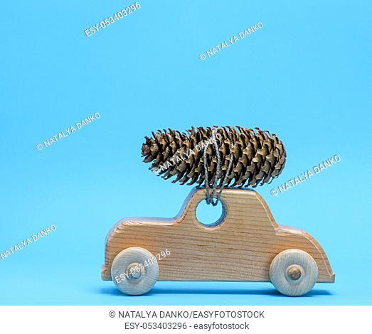 wooden toy car carries on top a pine cone on a blue background, Christmas background