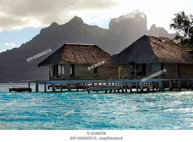 the destroyed thrown huts on water and island with palm trees in the ocean and mountains on a background