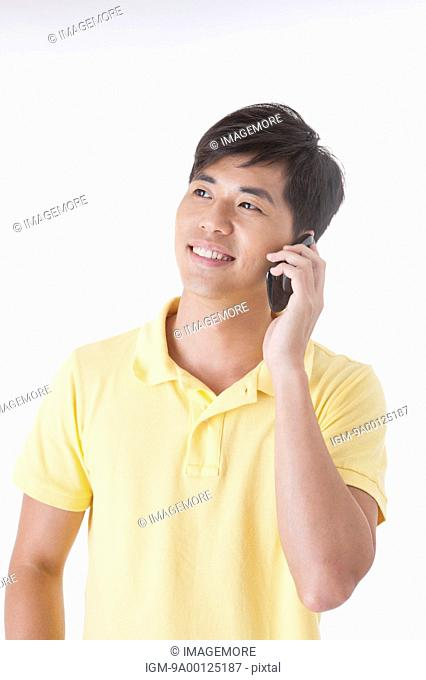 Young man looking away with smile and on the phone