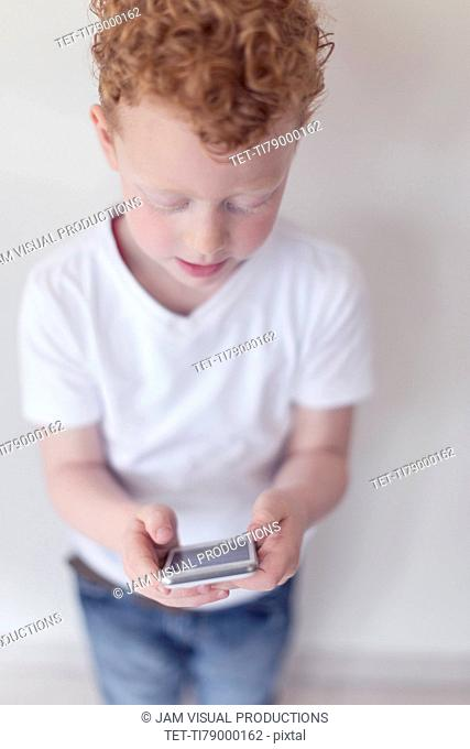 Boy (8-9) looking at smart phone