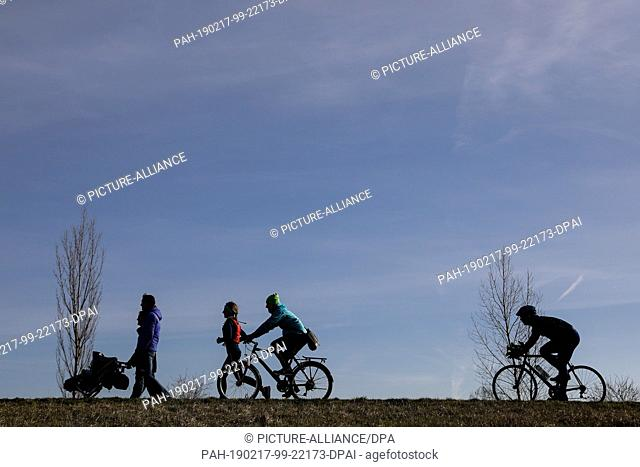 17 February 2019, Saxony, Markkleeberg: Cyclists, a family and a jogger use the spring weather for an excursion to Lake Cospuden in Markkleeberg near Leipzig