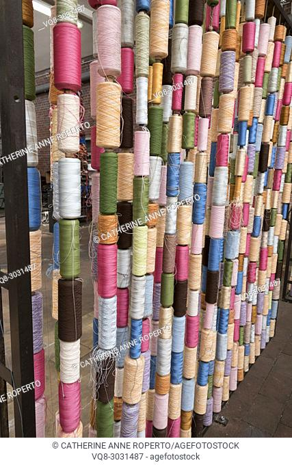 Vertical columns of vibrantly coloured thread standing sentinel like an architectural installation in traditional jacquard texile industry