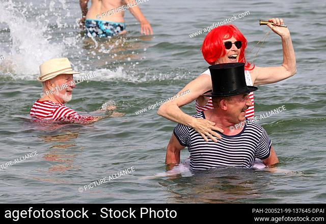 """21 May 2020, Mecklenburg-Western Pomerania, Warnemünde: Members of the winter swimming club """"""""Rostocker Seehunde e.V."""""""" dive into the eleven degree cold water..."""