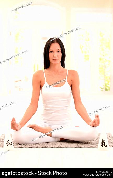 Attractive woman practicing yoga in lotus posture on ground, looking at camera