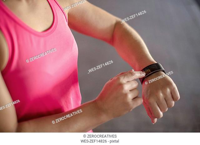 Woman adjustung settings of smartwatch for outdoor training