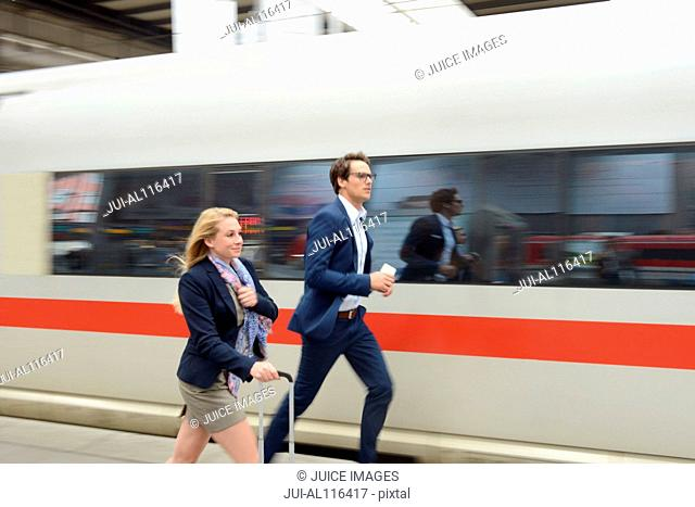 Businesswoman and man running for train at station, Munich, Bavaria, Germany, Europe