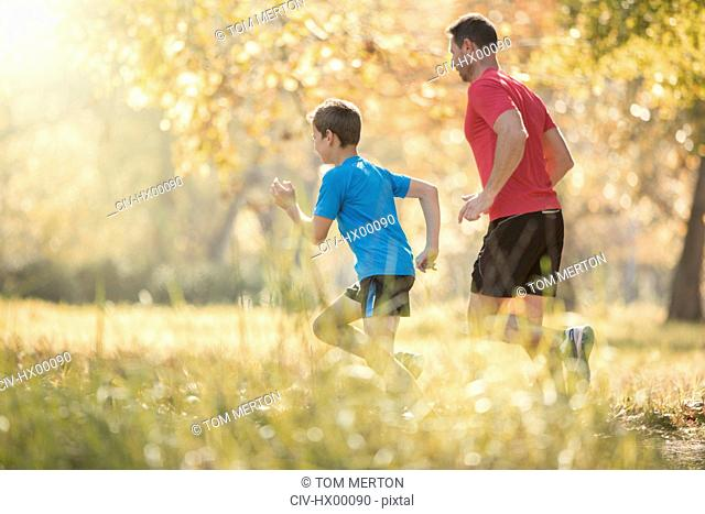 Father and son jogging in park