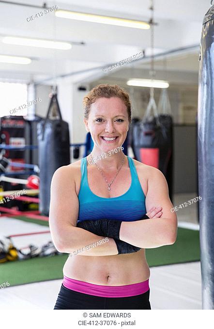 Portrait confident, smiling female boxer in gym