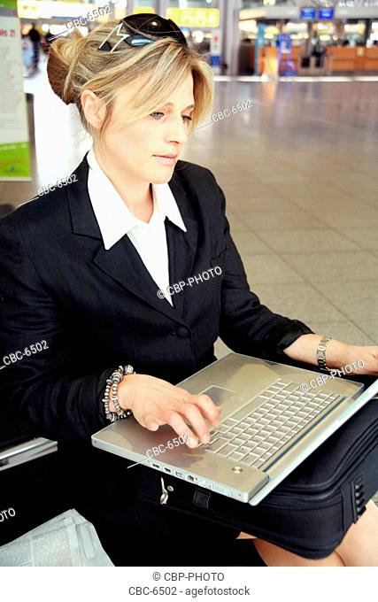 Young Businesswoman Using Laptop At The Airport