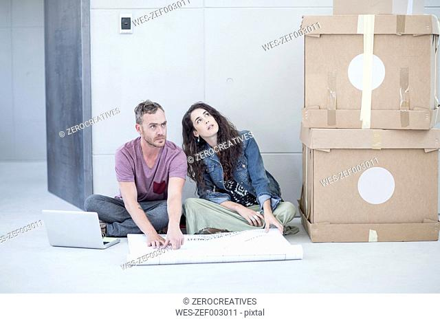 Creative office people sitting with a construction plan and boxes