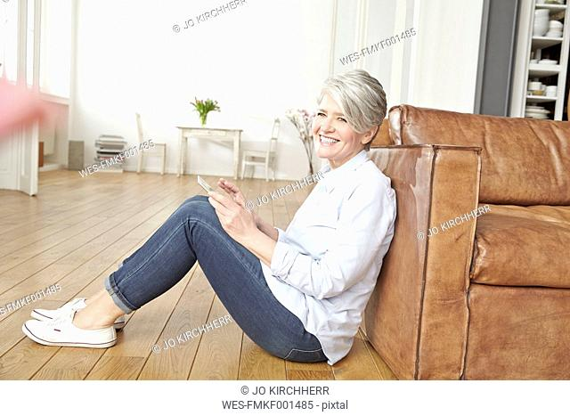 Mature woman sitting on floor using digital tablet