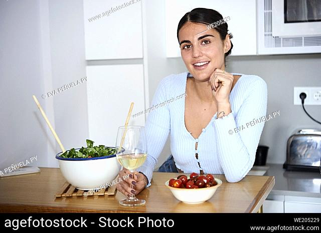 young woman preparing healthy food and enjoying her apartment