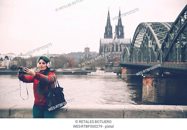 Germany, Cologne, woman with ear muff taking selfie with polaroid camera