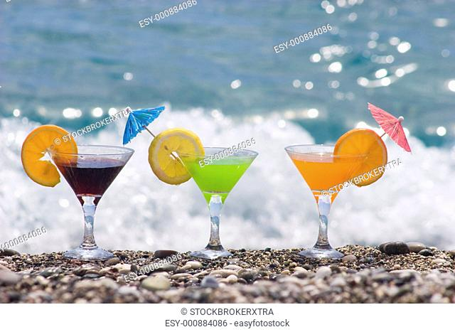 Close-up of three martini glasses filled with juice on river pebbles at background of surging wave