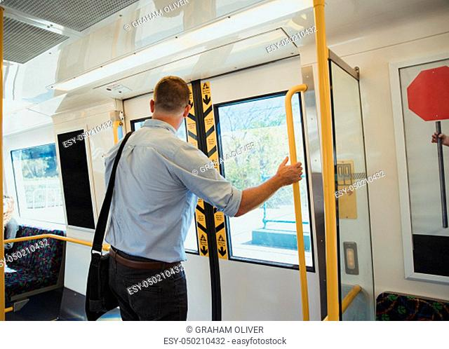 A rear-view shot of a mid-adult businessman standing on a train commuting to work, he is arriving at his destination