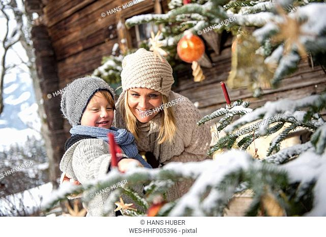 Austria, Altenmarkt-Zauchensee, mother and son looking at decorated Christmas tree in front of farmhouse
