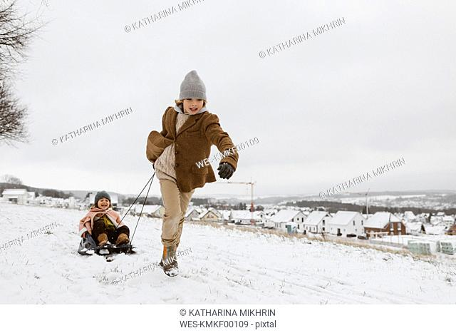 Boy pulling sledge with little sister in snow