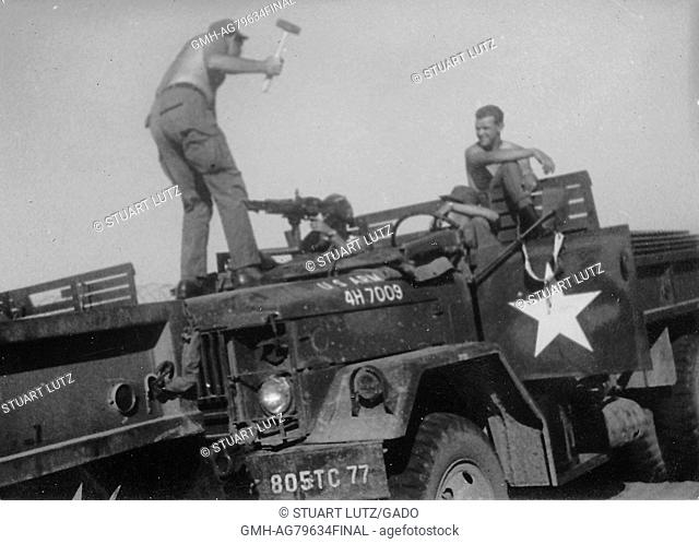 A photograph of four United States Army serviceman amusing each other on a parked M35 military truck, two of the soldiers watch in amusement while a soldier...