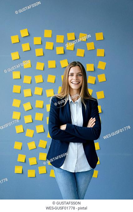 Yong businesswoman standing in front of wall, full of yellow sticky notes, with arms crossed