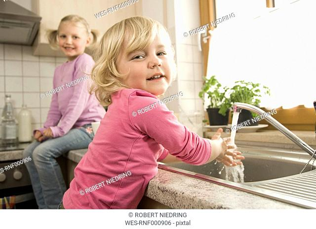Girl washing hands, sister sitting in background