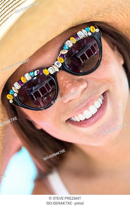 Close up portrait of young woman wearing sunglasses and sunhat