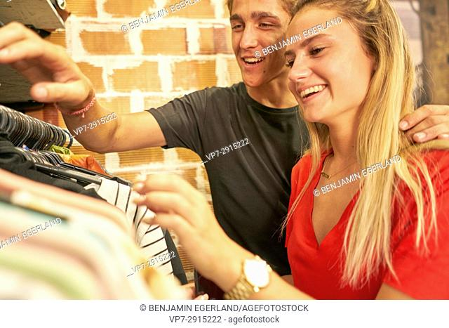 Happy young Dutch couple shopping together clothes in clothing store