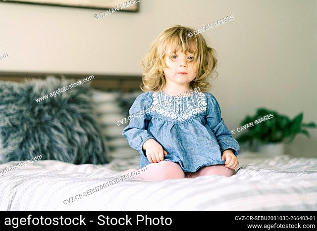 Little toddler girl taking a break from jumping on her parent's bed