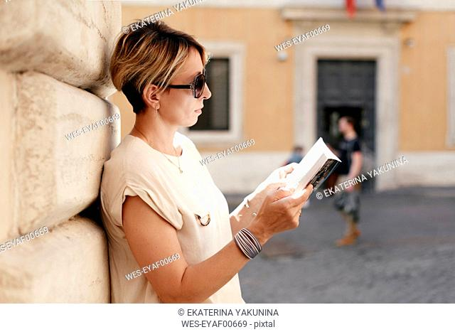 Woman looking into a guidebook in the city, Rome, Italy