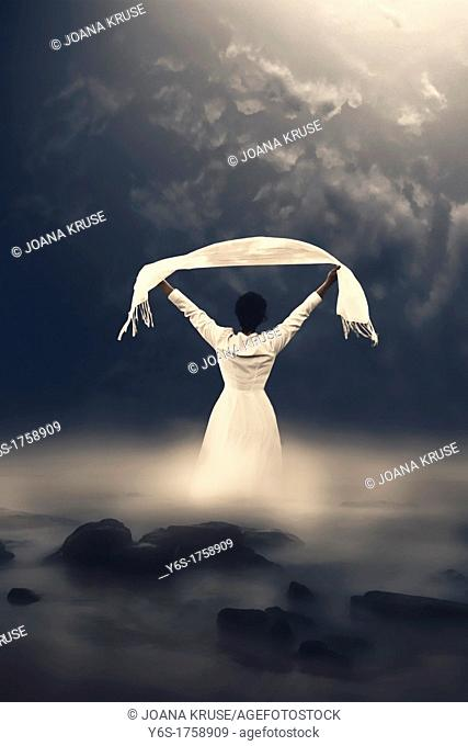 a woman in a white dress is coming out of the misty water