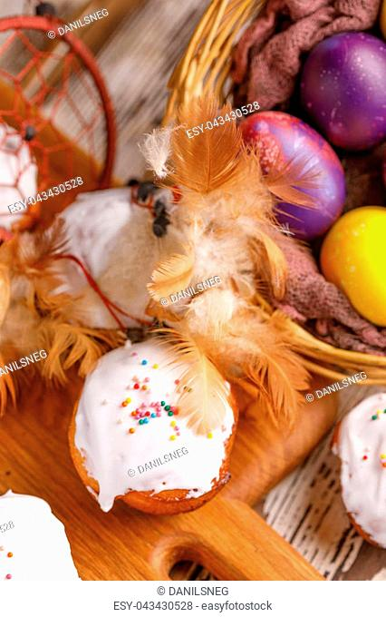 Easter cupcakes in sugar glaze and painted in unusual colors of eggs decorated with feathers of the dream catcher. View from above