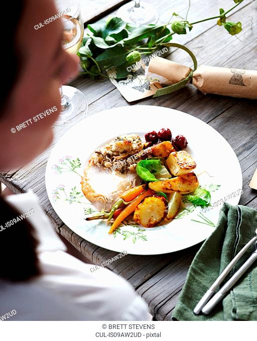 Over shoulder view of woman eating christmas dinner