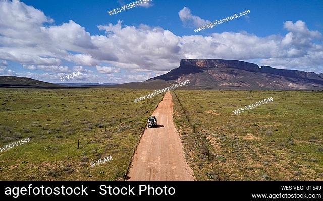 South Africa, Western Cape, Blanco, Aerial view of white 4x4 driving on dirt track towards mountains