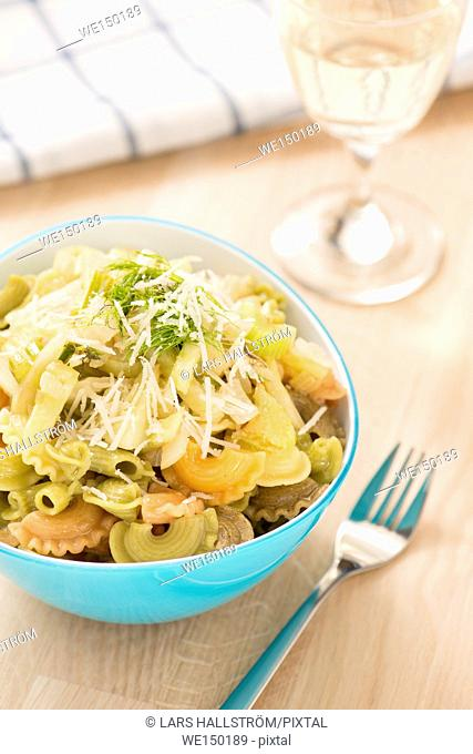 Pasta with fennel and onion in lemon dressing. Vegetarian food served with white wine. Healthy eating