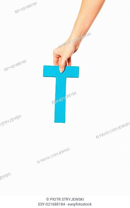 hand holding up the letter T from the top